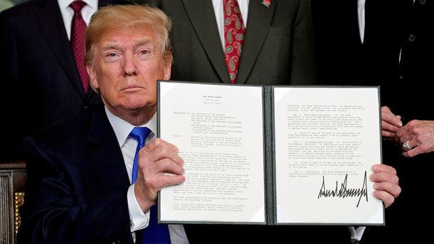 US President Donald Trump holds his signed memorandum on intellectual property tariffs on high-tech goods from China, at the White House in Washington, March 22, 2018.