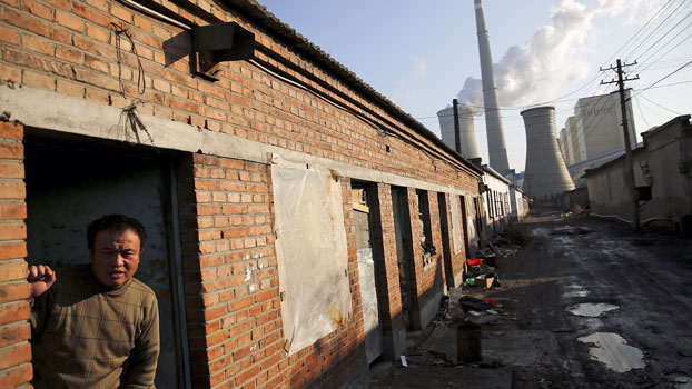 A migrant worker steps out of his accommodation in an area next to a coal-fired power plant in Beijing during a smog-free day and the last day of the city's first 'red alert' for air pollution, Dec. 10, 2015.