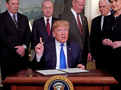 US President Donald Trump, surrounded by business leaders and administration officials, prepares to sign a memorandum on intellectual property tariffs on high-tech goods from China at the White House in Washington, March 22, 2018.