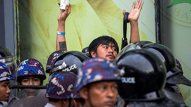 Myanmar police surround a demonstrator during an antiwar protest in Yangon, May 12, 2018.